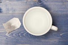 Tazza o tazza bianca con acqua calda e la borsa trasparenti di tè Concetto di tempo del tè Tazza riempita di acqua bollente e di  immagini stock libere da diritti