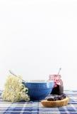 Tazza per la prima colazione con i fiori, pane, inceppamento Immagini Stock