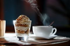 Tazza, piattino, cucchiaio e dessert in un vetro fotografia stock libera da diritti