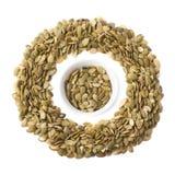Tazza piena dei semi di zucca isolati Immagine Stock