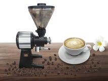 Tazza in pieno della bevanda del caffè sui semi di cacao torrefatti a fondo di legno fotografia stock