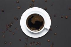 Tazza posta piana di caffè nero e dei chicchi di caffè sullo spazio scuro grigio della copia di vista superiore del fondo Concett fotografia stock libera da diritti