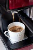 Tazza quasi in pieno di caffè Caffè che cade dalla macchina di caffè espresso Immagini Stock Libere da Diritti