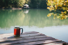 Tazza rossa che sta su un ponte vicino al lago Fotografia Stock Libera da Diritti