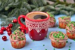 Tazza rossa con caffè ed i bigné di Natale con la crema del cioccolato Fotografie Stock