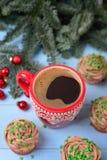 Tazza rossa con caffè ed i bigné di Natale con la crema del cioccolato, Fotografie Stock