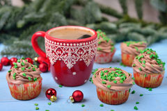 Tazza rossa con caffè ed i bigné di Natale su una parte posteriore di legno blu Fotografia Stock