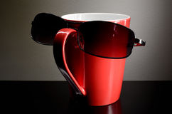 Tazza rossa con gli occhiali da sole Fotografia Stock