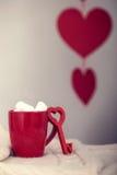 Tazza rossa con la bevanda e la caramella gommosa e molle calde Immagini Stock
