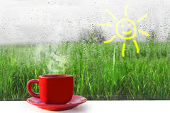 Tazza rossa di caffè caldo sulla tavola La vista dalla finestra sulla natura Pioggia fuori della finestra fotografia stock