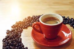 Tazza rossa di caffè espresso con i chicchi di caffè sulla tavola di legno Fotografia Stock Libera da Diritti