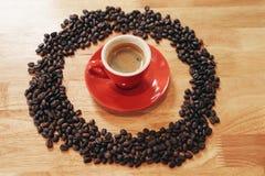 Tazza rossa di caffè espresso con le forme del cerchio fatte dai chicchi di caffè sulla tavola di legno Fotografia Stock