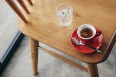 Tazza rossa di caffè espresso con tubo di livello sulla sedia di legno Fotografia Stock