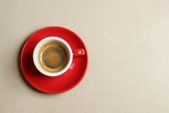 Tazza rossa di caffè espresso sul cuoio marrone chiaro del sedile Vista superiore Immagine Stock