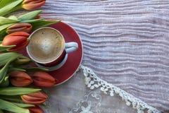 Tazza rossa di caffè nero con i tulipani rossi fotografia stock