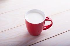 Tazza rossa di latte Fotografie Stock Libere da Diritti
