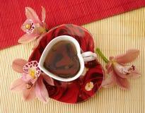 Tazza rossa di tè sotto forma di cuore con le orchidee dentellare sopra paglia Immagine Stock Libera da Diritti