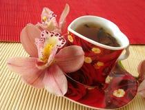 Tazza rossa di tè sotto forma di cuore con le orchidee dentellare sopra paglia Fotografia Stock