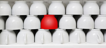 Tazza rossa in mezzo delle tazze di caffè macchiato Immagini Stock