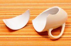 Tazza rotta, tazza rotta sul panno arancio Immagini Stock Libere da Diritti
