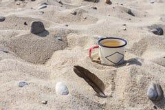 Tazza smaltata con acqua potabile pulita dal lago Baikal sulla riva del lago e della piuma nera del gabbiano nella sabbia Fotografie Stock