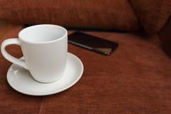 Tazza, tazza di caffè e smartphone della sfuocatura su tappeto rosso o sul sofà rosso Fotografie Stock
