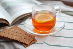 Tazza trasparente di tè con il limone, pane croccante della segale, un libro, luce naturale, prima colazione fotografie stock libere da diritti