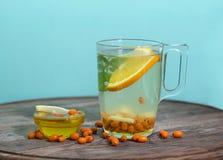 Tazza trasparente di tè con l'olivello spinoso, il miele ed il limone Fotografie Stock Libere da Diritti