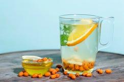 Tazza trasparente di tè con l'olivello spinoso, il miele ed il limone Immagine Stock