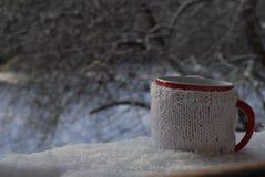 Tazza tricottata della bevanda calda nel fondo di inverno Immagini Stock