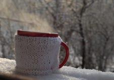 Tazza tricottata della bevanda calda nel fondo di inverno Fotografie Stock Libere da Diritti