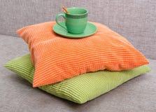Tazza verde ceramica con un piattino e un cucchiaino arancio su un mucchio Immagini Stock