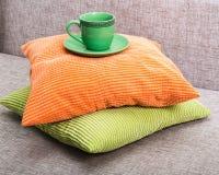 Tazza verde ceramica con un piattino su un mucchio da verde e da arancio Fotografia Stock Libera da Diritti