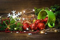 Tazza verde con i giocattoli e le luci di natale su fondo di legno isolato immagine stock
