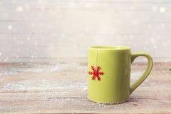 Tazza verde del tè di Natale con il fiocco di neve rosso sulla tavola di legno Fotografia Stock