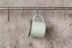 Tazza verde della latta che appende sulla ferrovia inossidabile sul backgroun della parete del cemento fotografia stock