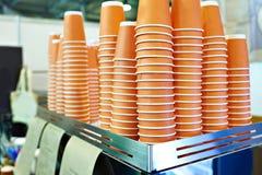Tazze arancio di carta per tè in caffè Immagine Stock
