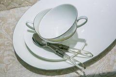 Tazze bianche con i cucchiai Fotografie Stock