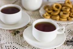 Tazze bianche con tè ed il piatto dei cracker sulla tavola con la tovaglia d'annata Immagine Stock Libera da Diritti