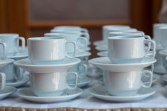 Tazze bianche per tè accatastato sulla tavola con i piatti per la pausa caffè Concetto di approvvigionamento Fotografia Stock Libera da Diritti