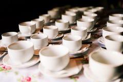 Tazze bianche sulla tabella Molte tazze vuote stanno in una fila sulla tavola Preparando per il banchetto Luce del giorno immagini stock