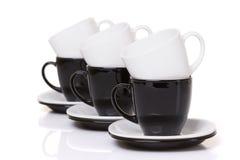 Tazze in bianco e nero sulla pila dei piatti Fotografia Stock