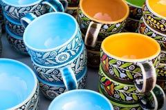Tazze blu e gialle variopinte nello stile etnico impilate sulla tavola di colore sopra fondo luminoso Immagini Stock