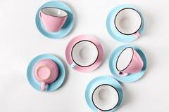 Tazze blu e rosa della porcellana elegante su fondo astratto Immagine Stock
