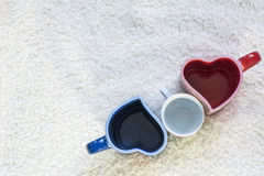 Tazze blu e rosse nella forma di cuore e di piccolo quello bianco Immagine Stock Libera da Diritti