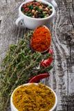 Tazze ceramiche bianche con differenti generi di spezie su vecchio di legno Fotografia Stock
