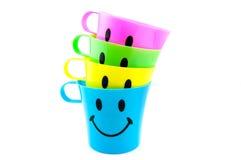 Tazze colorate con il fronte felice Immagine Stock