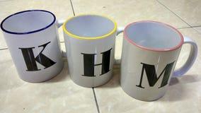 3 tazze con l'alfabeto Fotografia Stock Libera da Diritti