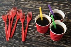Tazze con la bevanda e le forcelle rosse Fotografie Stock