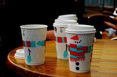 Tazze da portar via di Coffe nell'inverno sulla tavola Immagine Stock Libera da Diritti